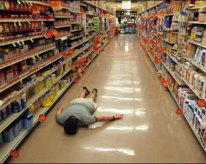 Man lying face down in an empty supermarket isle