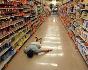 Man lying face down in an empty supermarket isle